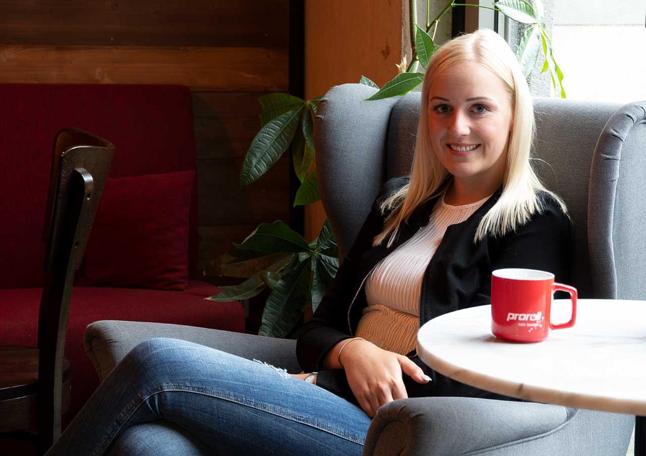 Une femme blonde est assise sur une chaise à oreilles.